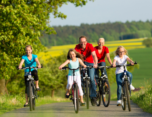 Family with three girls having a weekend excursion on their bikes or bicycles on a summer day in beautiful landscape